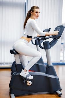 Mujer de ciclismo interior haciendo ejercicio cardiovascular en bicicleta en bicicleta de gimnasio en el interior.