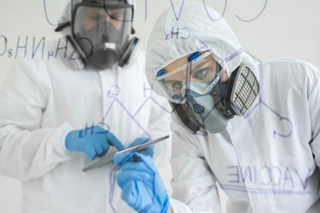 Mujer científica en laboratorio escribe fórmula química. concepto de covid-19