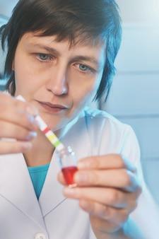 Mujer científico en bata blanca trabajando en laboratorio