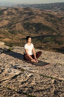 Mujer en la cima de la montaña meditando