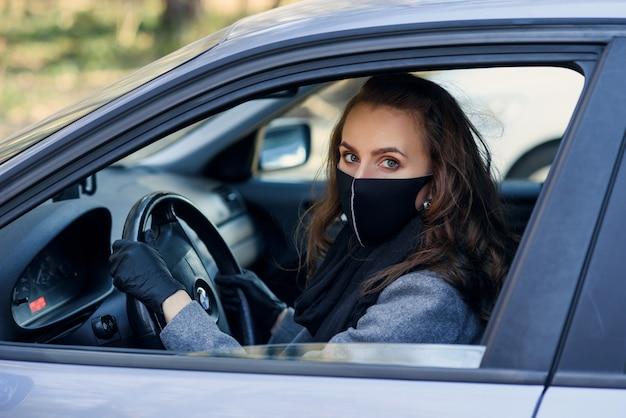 Mujer en la ciudad persona en una máscara. tema coronavirus. mujer junto al auto.
