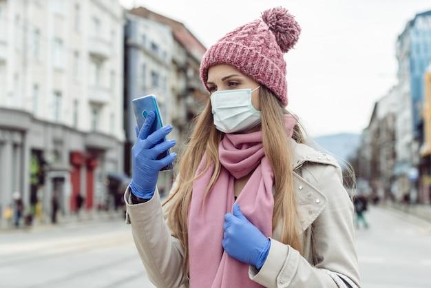 Mujer en una ciudad vacía encerrada revisando las noticias en su teléfono