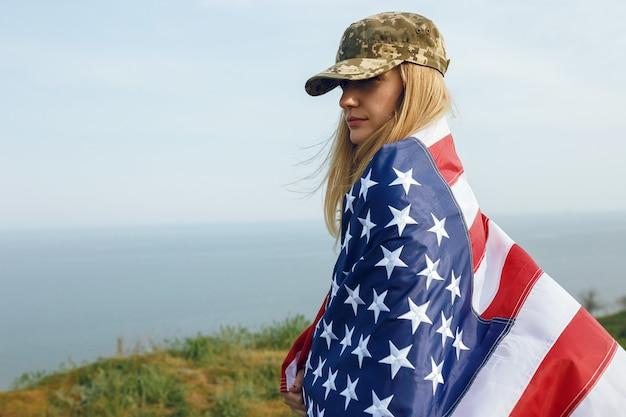 Mujer civil con gorra militar de su marido. una viuda con una bandera de los estados unidos se fue sin su marido. memorial day a los soldados caídos en la guerra. el 27 de mayo es un día conmemorativo.