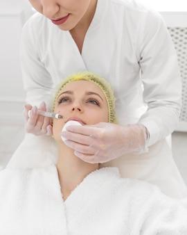 Mujer en la clínica de belleza para tratamiento de relleno