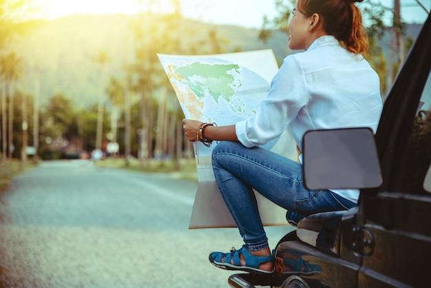 Mujer en el coche por viaje con un mapa.