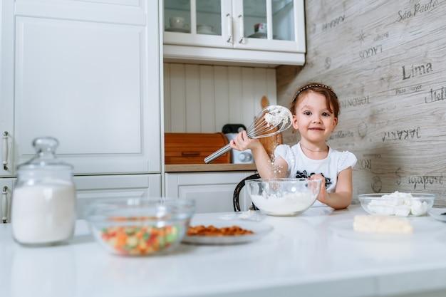 La mujer de la cocina bate la masa con un batidor