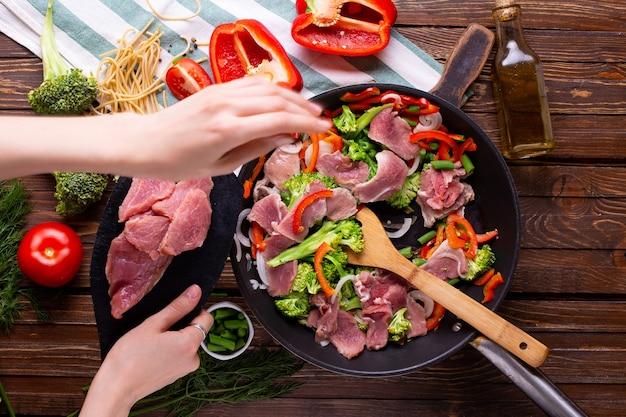 Mujer cocina carne con verduras en una sartén en casa vista superior