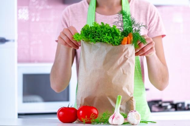 Mujer de cocina en delantal con una bolsa de papel artesanal llena de verduras orgánicas frescas en la cocina. comida sana y dieta balanceada