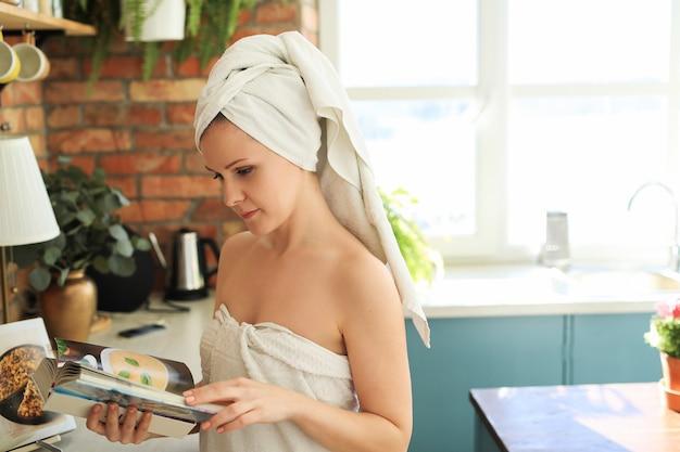 Mujer en la cocina con una toalla sobre su cabeza después de la ducha