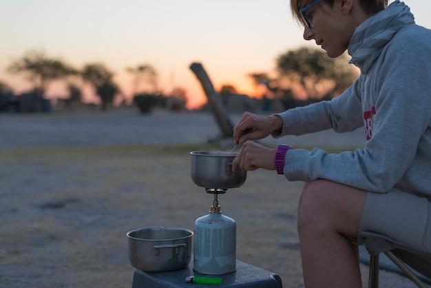 Mujer cocinando con estufa de gas en camping al atardecer. quemador de gas, olla y humo del agua hirviendo.