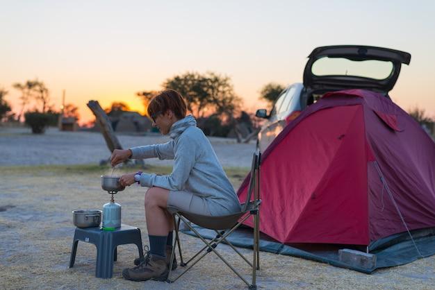 Mujer cocinando con estufa de gas en camping al atardecer.