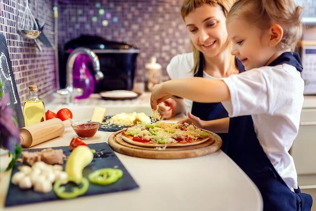 Mujer cocinando con niña