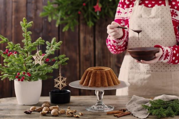 Mujer cocinando pastel de navidad en la cocina de madera