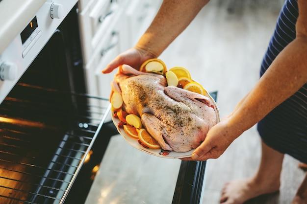 Mujer cocinando pato de navidad poniendo pato crudo con verduras en el horno.