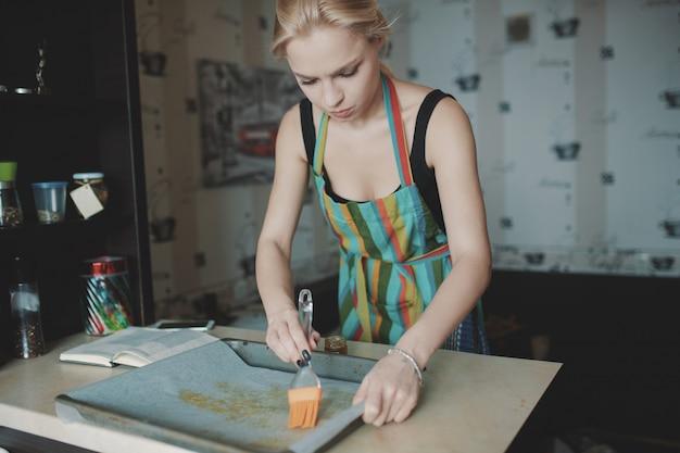 Mujer cocinando pizza en la cocina