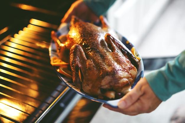 Mujer cocinar pato con verduras y ponerlo del horno.