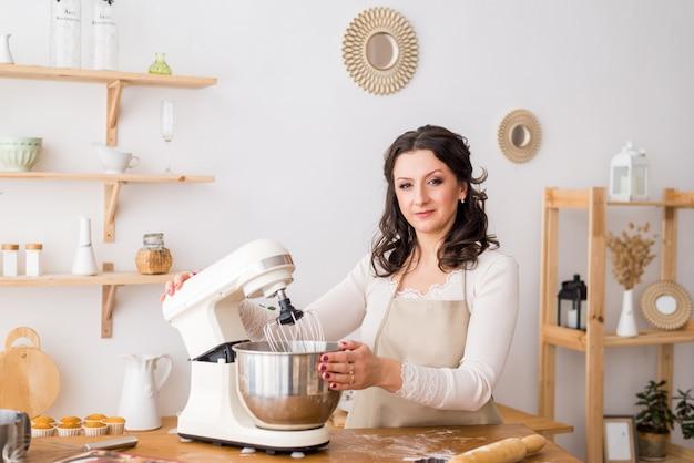 Mujer cocinera en casa en la cocina trabajando con una batidora