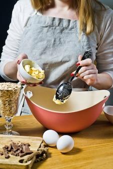 Mujer cocinera prepara galletas de avena, pone mantequilla en un tazón. ingredientes copos de avena, mantequilla, azúcar, huevos, chocolate.