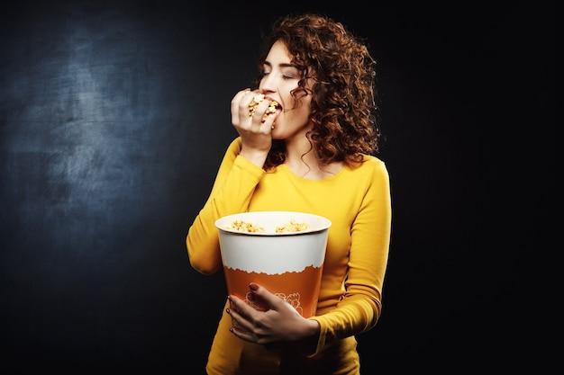Mujer codiciosa agarra un puñado de palomitas de maíz con los ojos cerrados