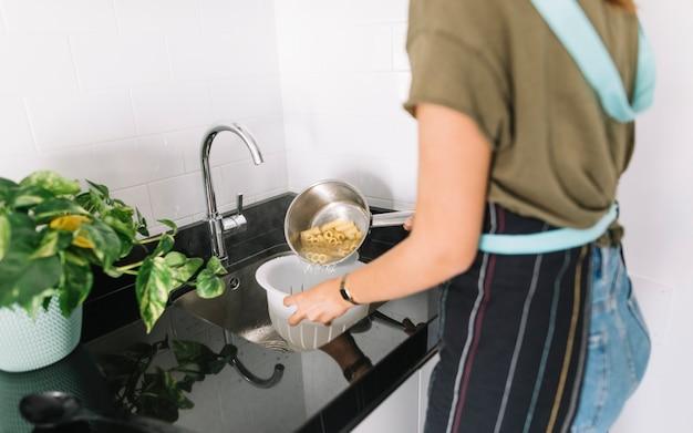 Mujer colar pasta hervida en el colador