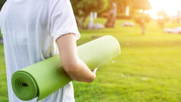 Mujer con colchoneta de yoga en el parque