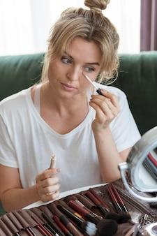 Mujer con una colección de pinceles de maquillaje.