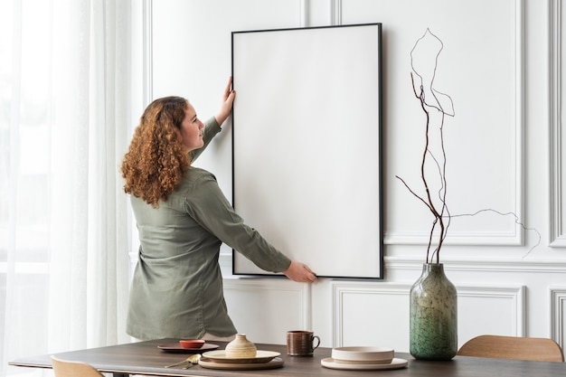 Mujer colgando marco de imagen en blanco en la pared