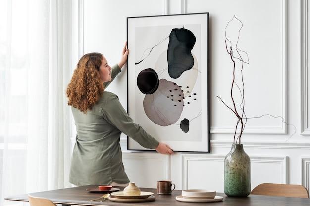 Mujer colgando marco de imagen en la pared con espacio de diseño
