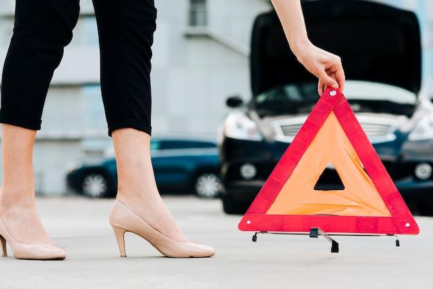 Mujer colocando señal de emergencia