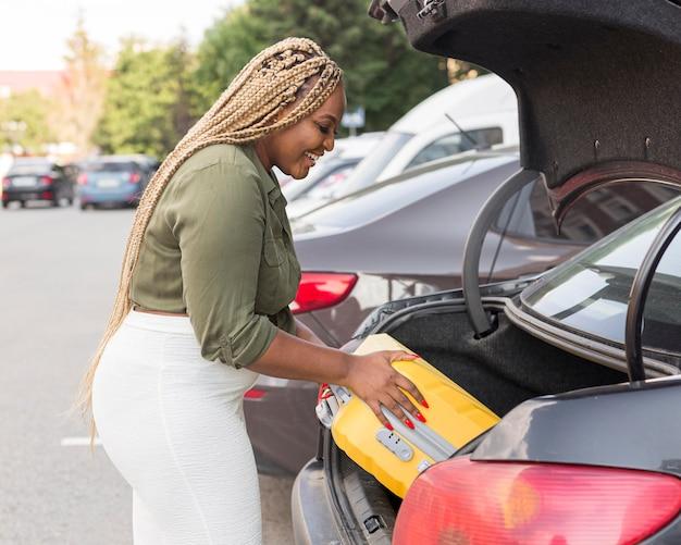 Mujer colocando su equipaje en su baúl