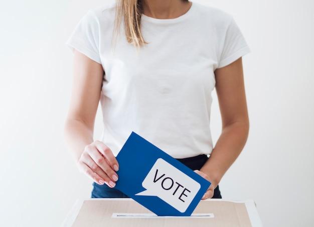 Mujer colocando tarjeta azul con mensaje de votación en un cuadro