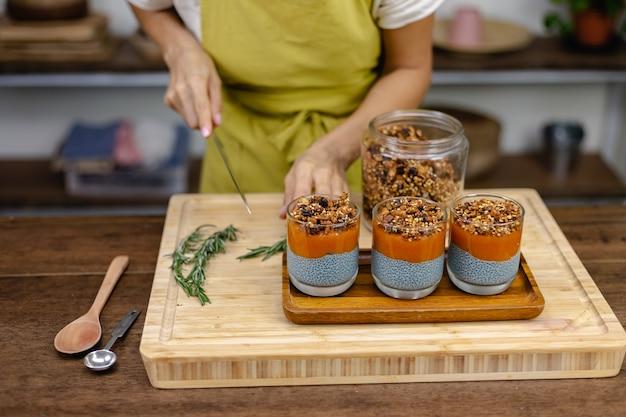 Mujer con coloridos postres dulces saludables budines de chía hechos de leche de almendras, extracto de espirulina azul, semillas de chía, mermelada de mango pappaya y granola casera. en la mesa de madera en la cocina de casa.