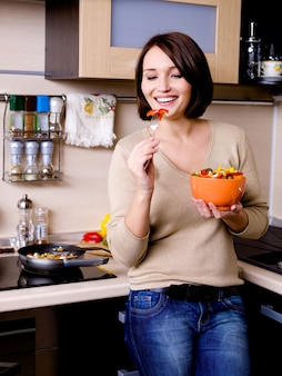 Mujer come ensalada de verduras