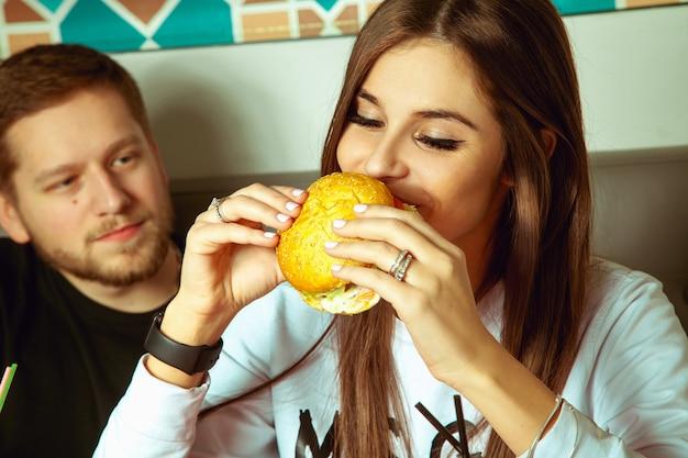 Mujer come hamburguesa en el café con su novio