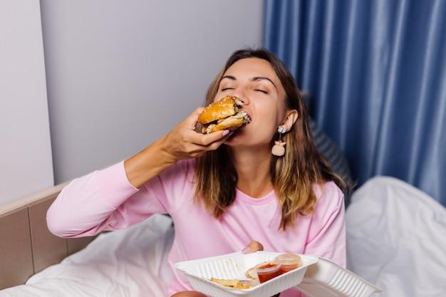Mujer come hamburguesa en casa