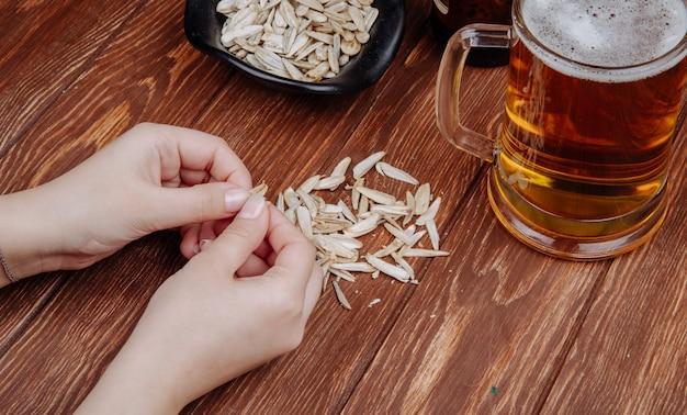Una mujer come semillas de girasol aperitivo salado con una jarra de cerveza en vista lateral de madera rústica
