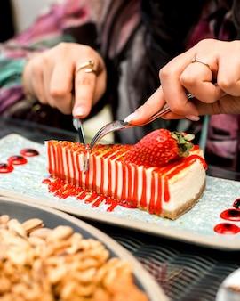 Mujer come tarta de fresa con cuchillo y tenedor