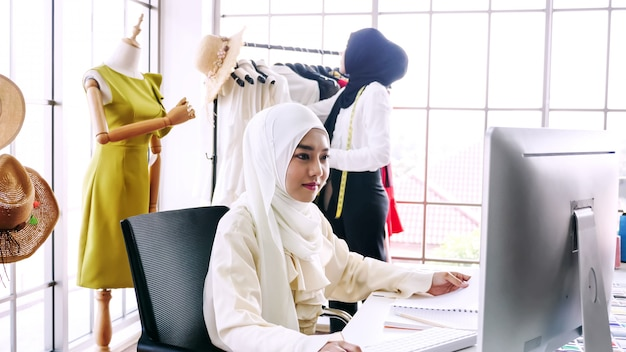 Mujer comerciante islámica comprobar pedidos en línea en la oficina.