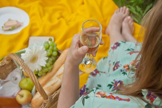 La mujer en la comida campestre se sienta en la cubierta amarilla y sostiene la copa de vino.