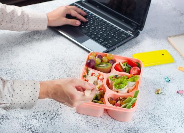 Mujer comiendo un almuerzo de la caja de almuerzo en la mesa de la oficina