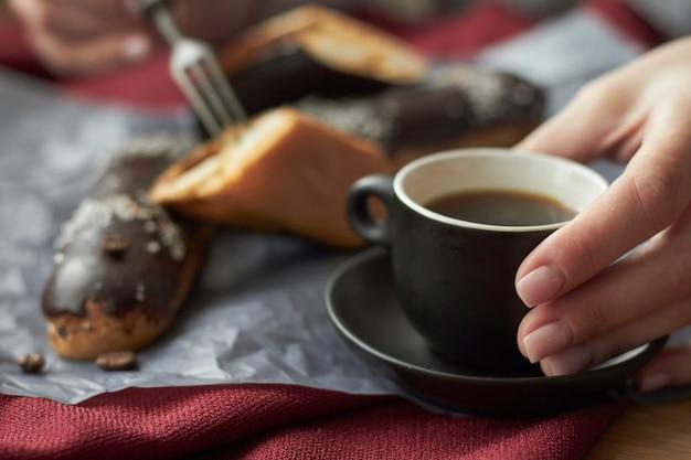 Mujer comiendo canutillos rellenos de crema, canutillos franceses tradicionales con chocolate y una taza de café exprés.