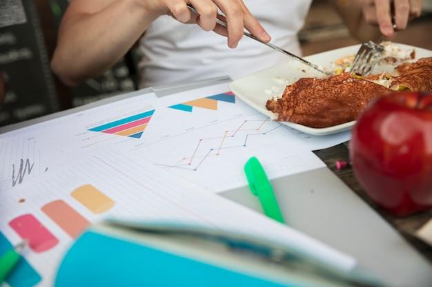 Mujer comiendo comida en la mesa cerca de gráficos y diagramas