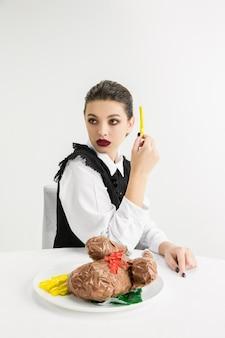 La mujer está comiendo comida de plástico