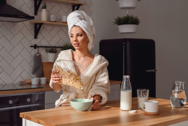 Mujer comiendo copos de maíz en el desayuno mientras está de pie en la cocina moderna en casa
