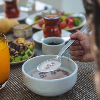 Mujer comiendo cremosa sopa de champiñones, jugo de naranja alrededor