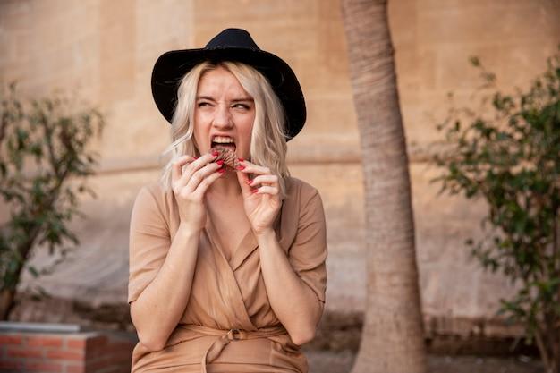 Mujer comiendo cupcake afuera