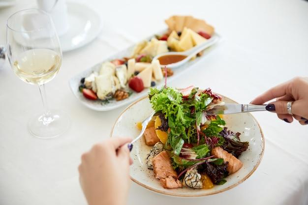Mujer está comiendo ensalada de cerdo con lechuga, queso y una copa de vino
