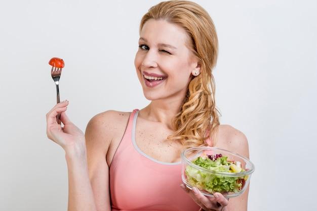 Mujer comiendo una ensalada de lechuga