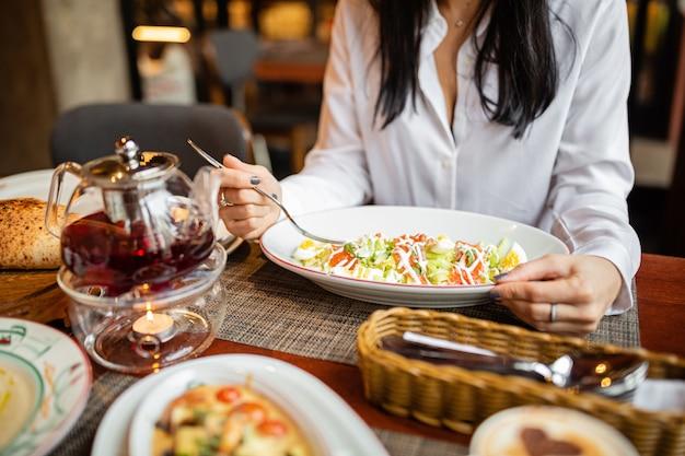 Mujer comiendo ensalada saludable en un restaurante