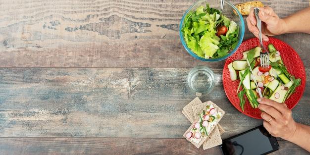 Mujer comiendo una ensalada vegana. varios vegetales sobre madera